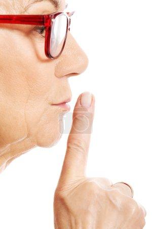 Elderly woman is having finger on her lips. Profile.