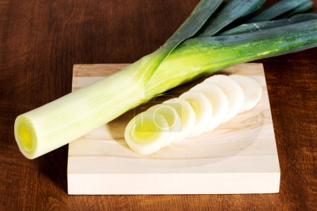 Photo for Green fresh leek and its slices on cutting board. - Royalty Free Image