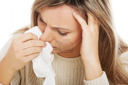Young woman with tissues crying or having runny nose.