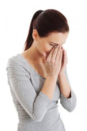 Young beautiful woman touching her nose.