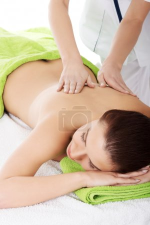 Beautiful woman lying on bed in spa salon.