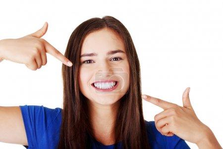 Photo pour Belle femme pointant sur ses dents blanches parfaites. isolé sur blanc. - image libre de droit