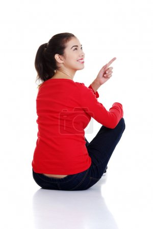 Happy young woman pointing on copy space.