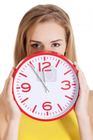 Beautiful caucasian casual woman holding red clock.