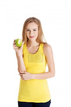 Beautiful causal caucasian woman holding fresh green apple with missing bite