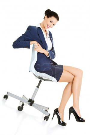 Photo for Beautiful successful businesswoman sitting on ofice chair and smiling, isolated on white - Royalty Free Image