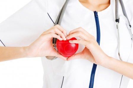 Photo pour Jeune infirmière avec le cœur à la main, isolée sur blanc . - image libre de droit
