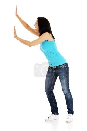Photo pour Femme poussant quelque chose d'imaginaire isolé sur un fond blanc - image libre de droit