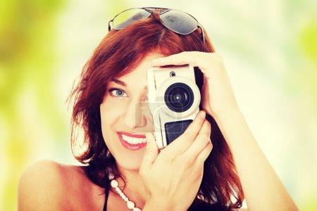 Foto de Joven hermosa mujer sonriente sosteniendo una micro cuatro tercios Foto cámara. - Imagen libre de derechos