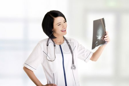 Female doctor or nurse looking at radiography photo
