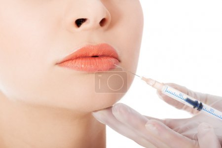 Young beautiful woman doing injection into mouth.