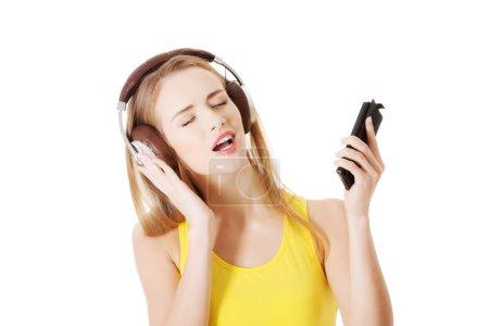 Photo pour Belle jeune femme écoutant de la musique avec un casque. isolé sur blanc. - image libre de droit