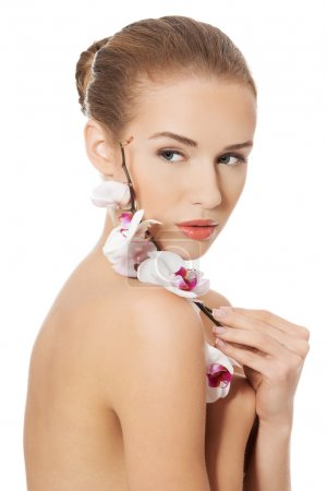 Nude naked woman having white flower on shoulders.