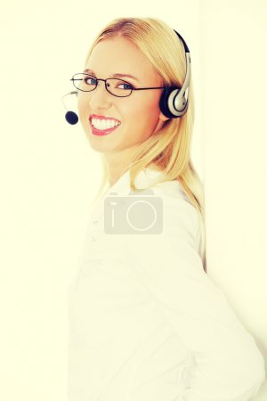 Photo for Portrait of a successful young female call centre employee wearing a headset against white background - Royalty Free Image