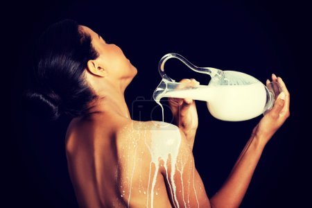 Photo pour Belle femme nue est coulée de lait sur son dos. sur fond noir. - image libre de droit