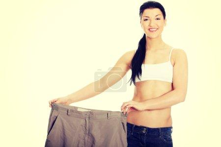 Photo pour Jeune femme heureuse montrant combien de poids elle a perdu . - image libre de droit