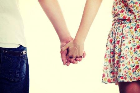 Photo pour Paire d'amoureux. jeune couple est debout une face arrière et tenant par la main. - image libre de droit