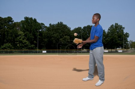 Photo for A black African American teenage man baseball pitcher getting ready to throw a ball in a game - Royalty Free Image