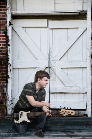 Photo for Young man holding a bass guitar musical instrument - Royalty Free Image