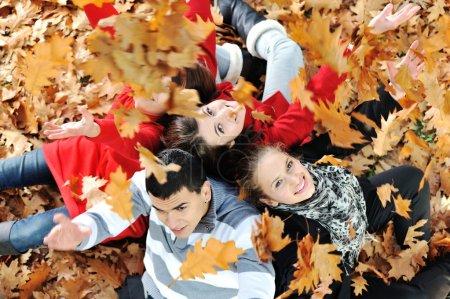 Photo pour Joyeux groupe de jeunes amis ensemble dans le parc de la chute - image libre de droit