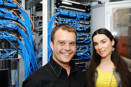 Photo pour Deux administrateurs, mâles et femelles, à la salle des serveurs - image libre de droit