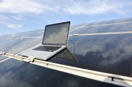 Foto de Ordenador portátil en paneles solares fotovoltaicos contra el cielo azul - Imagen libre de derechos