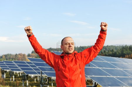 Success, engineer in solar panel fields with arms up
