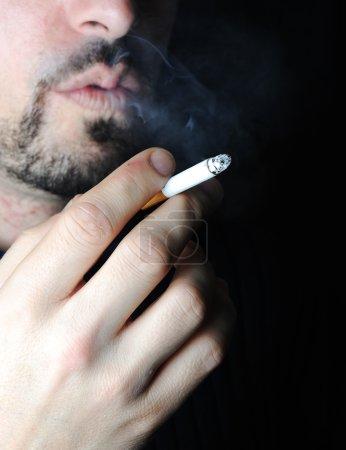Man smoking in dark with visible smoke