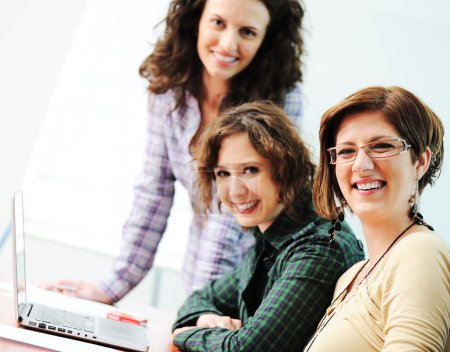 Group of young happy looking into laptop working on it