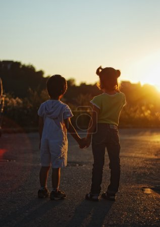 Romantic vision of two children standing together outdoor