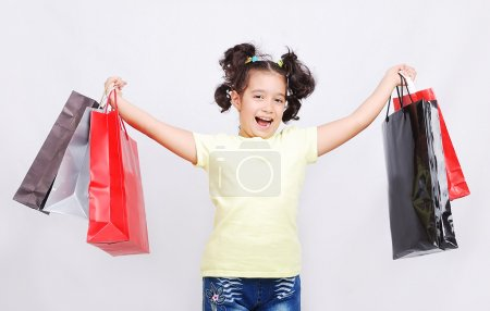 Cute little girl with bags for shopping