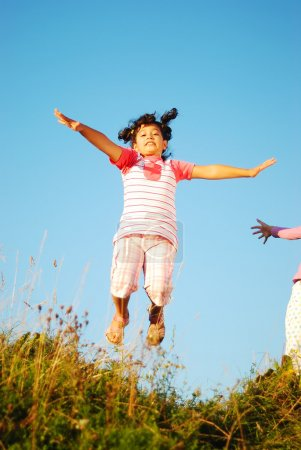 Happy little girl jumping and joying in nature