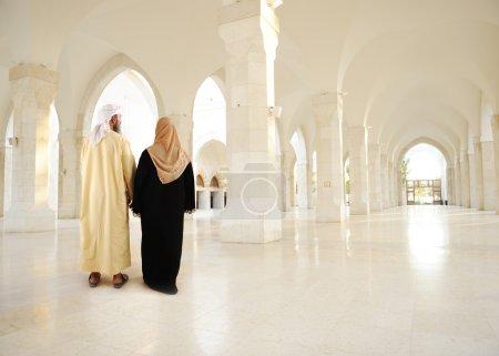 Photo pour Couple arabe musulmane à l'intérieur du grand bâtiment moderne vide oriental - image libre de droit