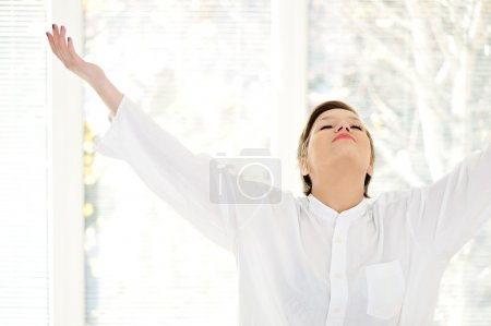 Relaxed young woman at home with raised arms...
