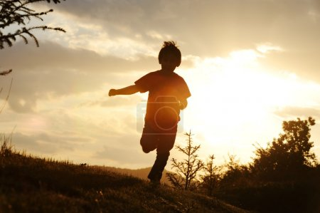 Photo for Kid running on meadow silhouette - Royalty Free Image