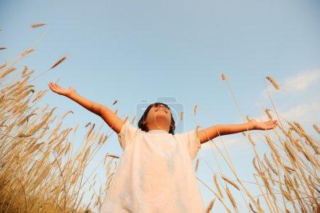 Photo pour Enfant au champ de blé à bras ouverts - image libre de droit