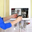 Repairman fixing a gas heating with screwdriver...