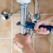 Hands of a plumber with sink and wrench...