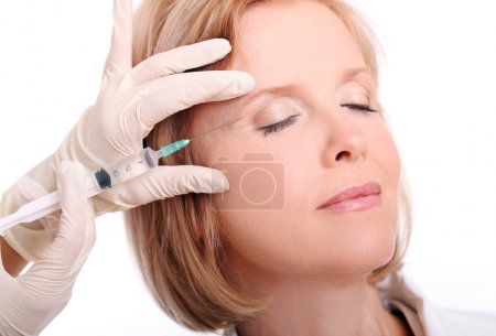 Woman having face injection