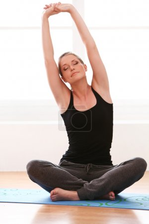 Beautiful woman doing yoga exercises at home