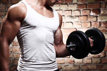 Photo for Muscular guy doing exercises with dumbbell against a brick wall - Royalty Free Image