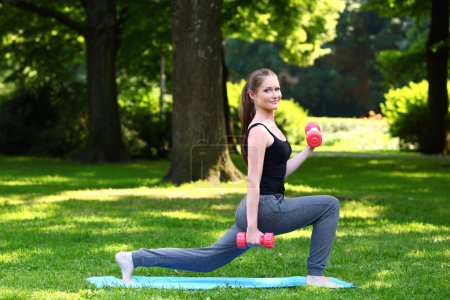Young woman doing lunges with dumbbells