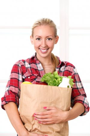 Photo for Happy smiling woman holding a grocery bag - Royalty Free Image
