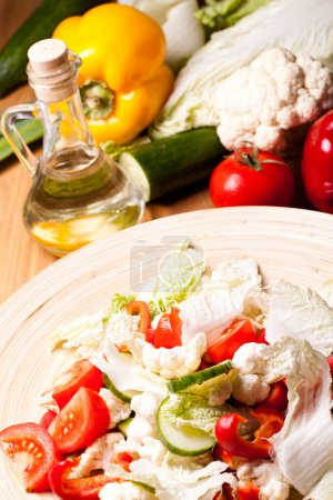Wooden plate with vegetable salad