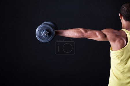 Photo for Strong and muscular guy with dumbbell over black background - Royalty Free Image