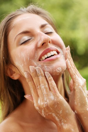Happy woman washing her face