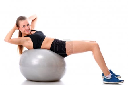 Smiling woman doing exercises with fitness ball