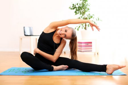 Beautiful woman do yoga exercises at home