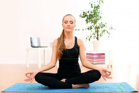 Young and beautiful woman meditate at home