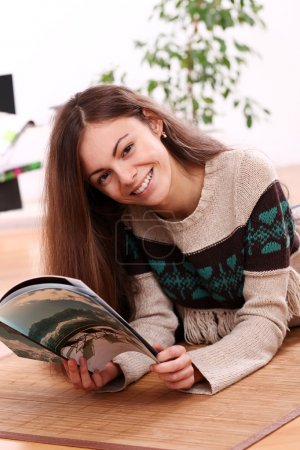 Cute young woman reading magazine at home